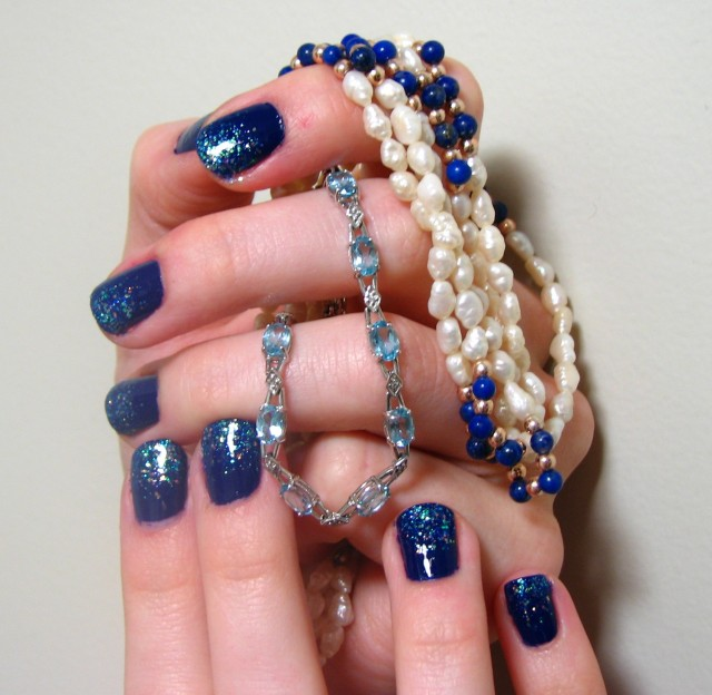 Syl's first attempt at nail art, displayed with some of the loot from Watersdeep, place that inspired this glittery blue manicure.